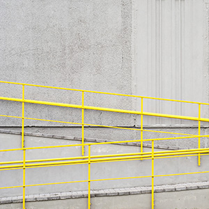 Zigzag concrete ramp with yellow handrails